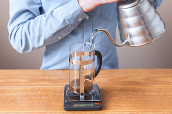 Person gießt Wasser in French Press